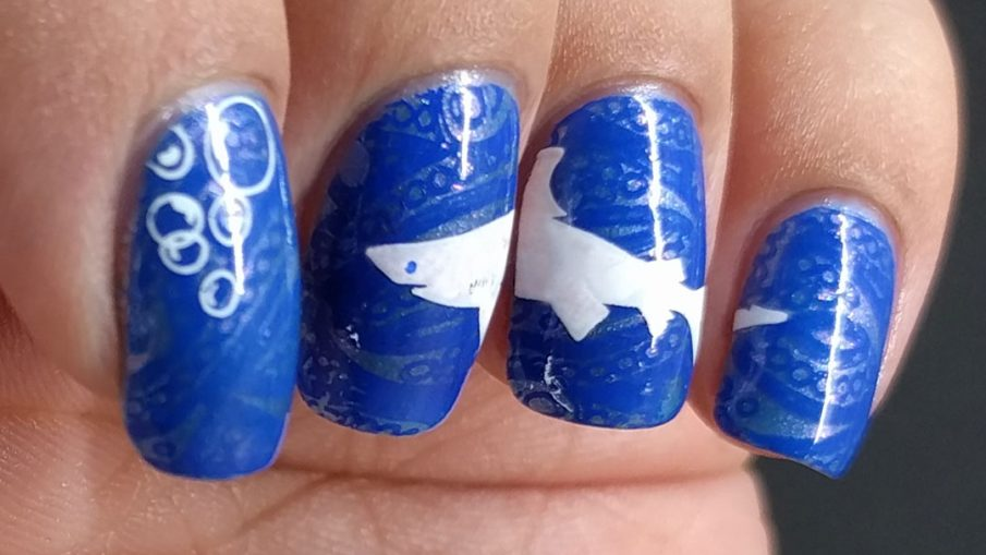 La-sea with a Chance of Sharks - Hermit Werds - nail art with elegant blue lace ocean with a great white shark stamped on top