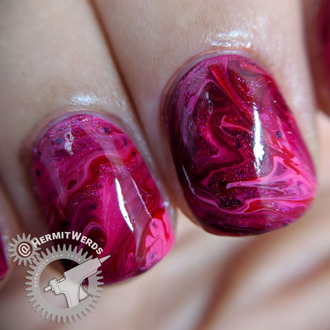 Pink to Red fluid art - Hermit Werds - macro shot of pink holographic, pink, and red fluid nail art