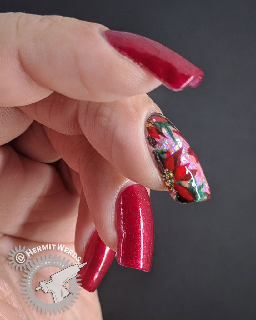 Glittery Poinsettia - Hermit Werds - red manicure with a pink accent nail covered with iridescent glitter and freehand painted holly leaves and poinsettia flowers (Robin Moses)