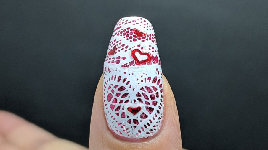 Lacy Heart - Hermit Werds - lace stamping in a heart shape over a glittery pink background with red heart sequins on top