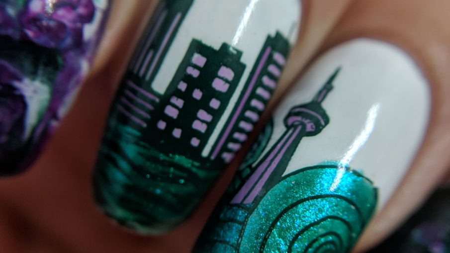 Seattle Tribute - Hermit Werds - nail art for Seattle with a cityscape and the Space Needle bracketed with a smoosh marble in emerald green and purples.