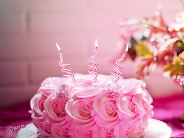 Pink cake with three fancy candles sticking out of it.