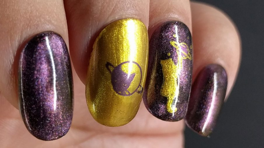 Purple/pink magnetic polish with golden space cats stamped on top.