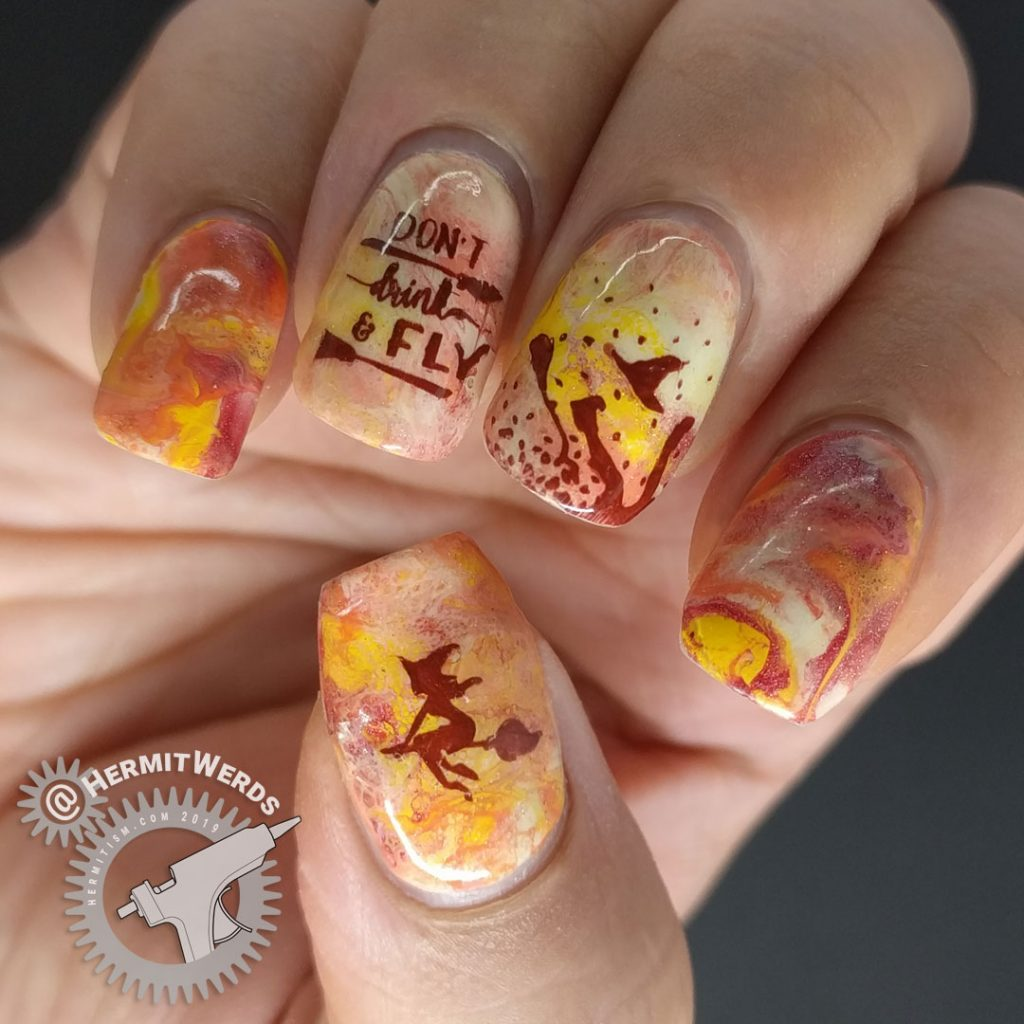 Orange, yellow, and coral fluid art nails with witch nail art stamped on top. Don't drink and fly!