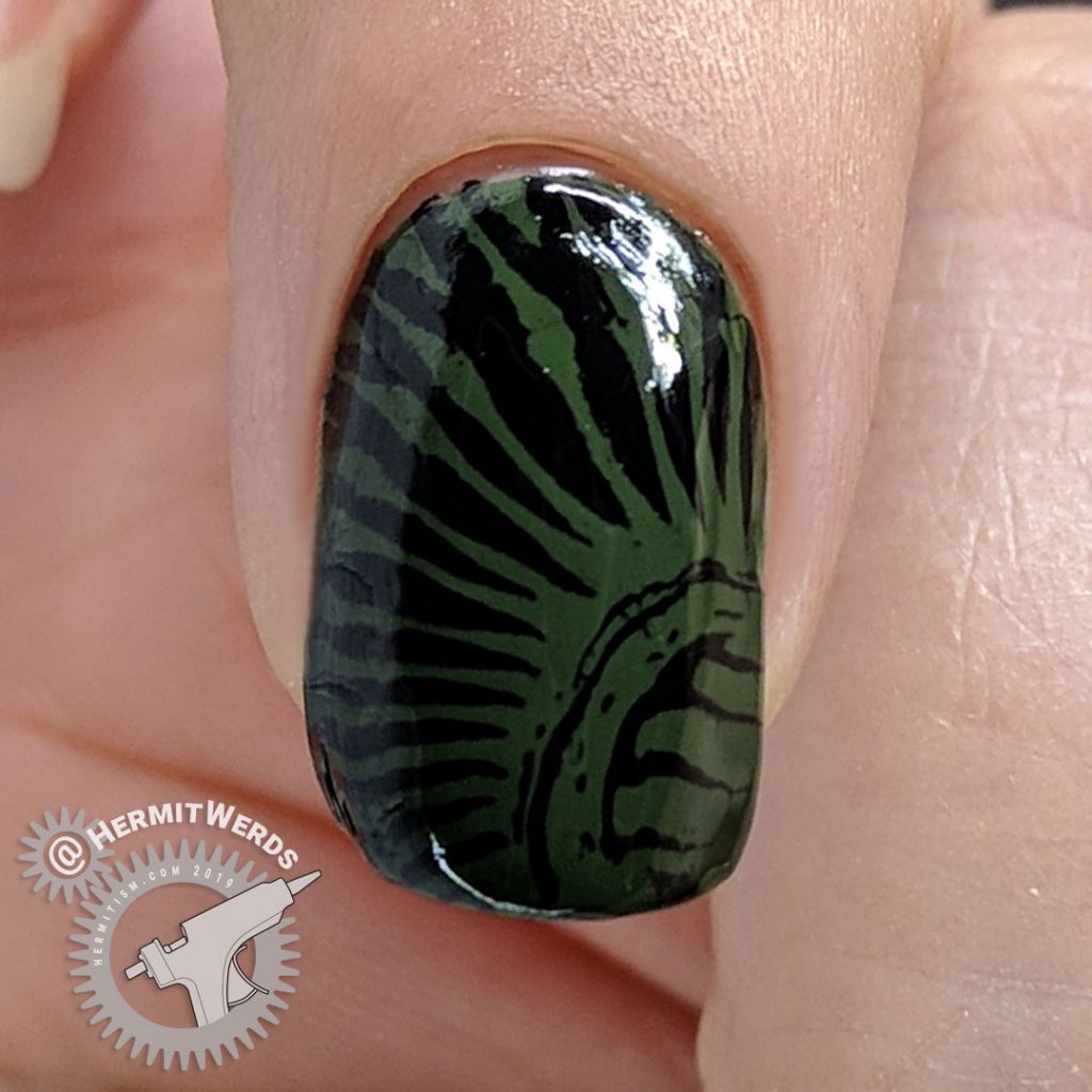 Olive green nail with creepy pattern.