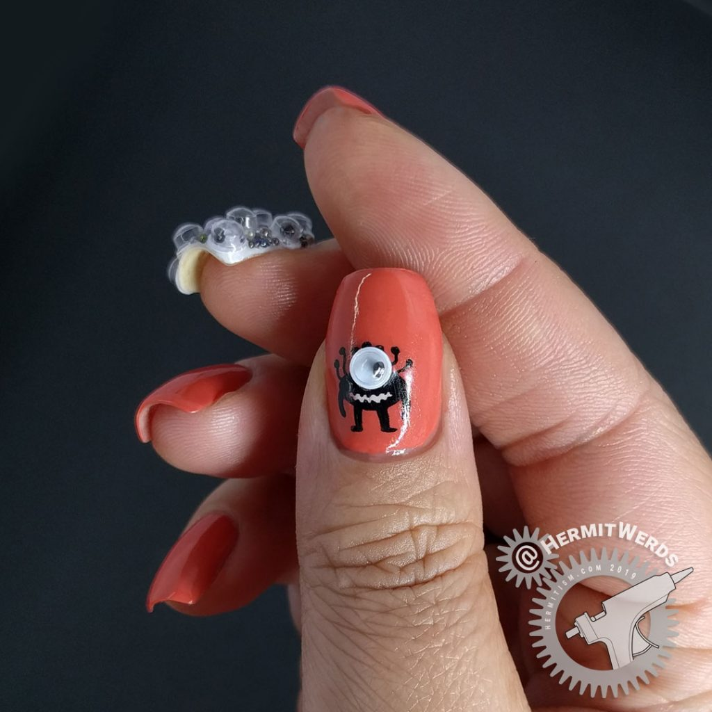 Crab apple colored nail art with googly eyes and a wee monster on the thumb.