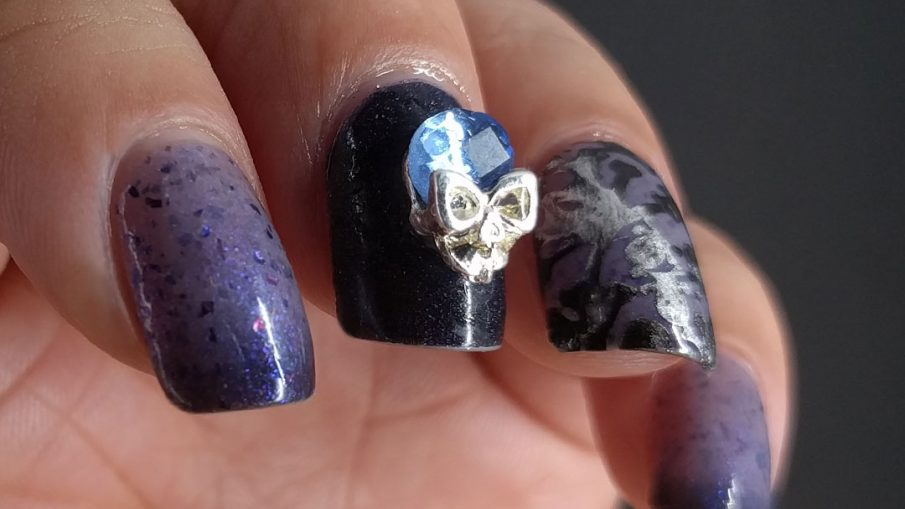 Blurple thermal nail art with skulls and skeletons and a blue and silver rhinestone.