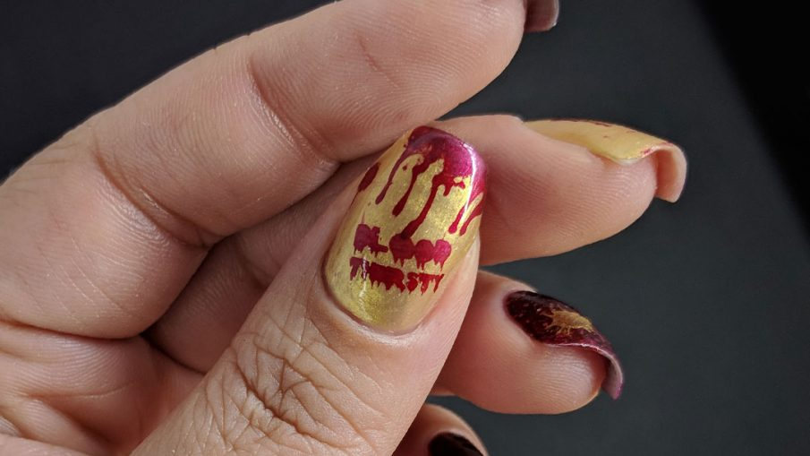 Red and gold metallic bloody vampire nail art for Halloween.