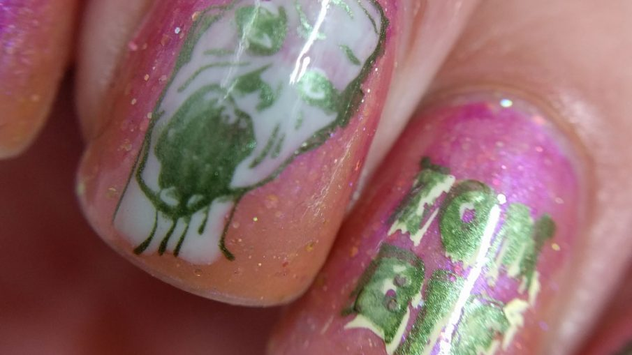 A delicately gruesome zombie nail art using a translucent shimmery orange polish and soft metallic green zombies.