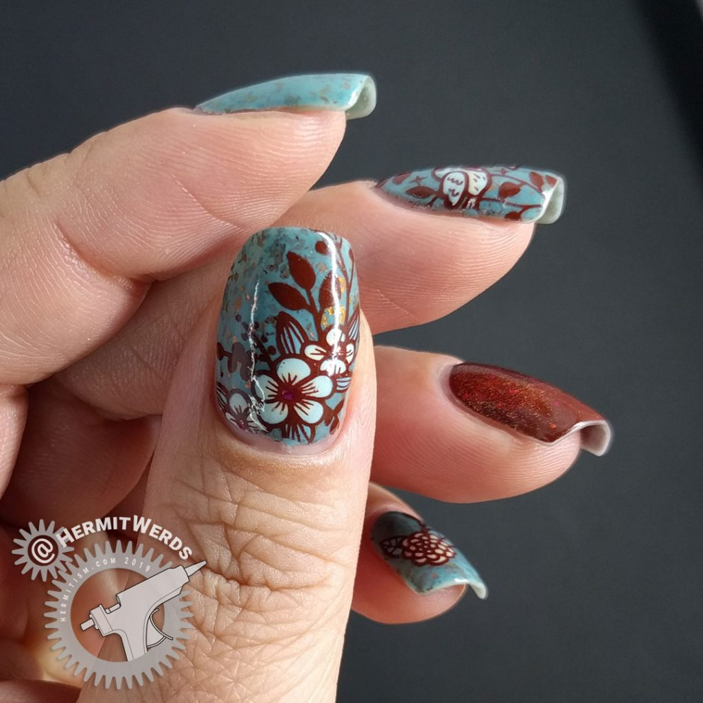 Autumnal nail art with a little blue bird against a robin blue crelly full of pink/orange/red flakies.