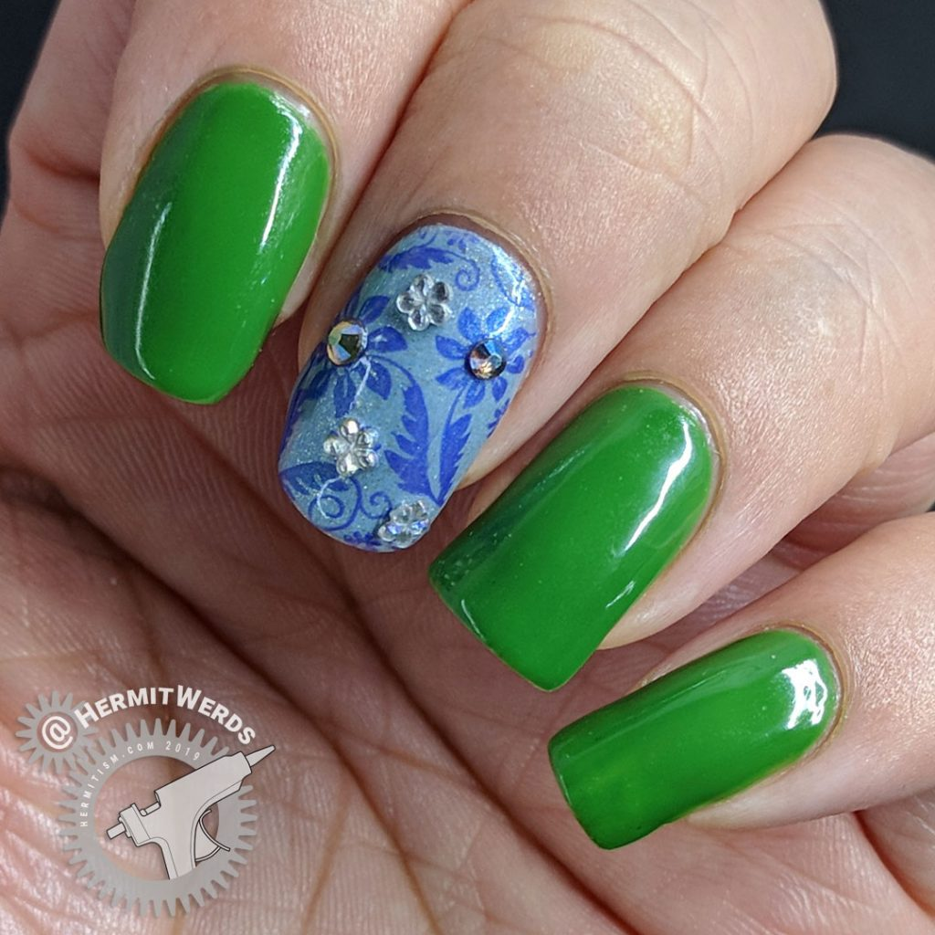 Floral nail art featuring Pantone's Eden and blue floral accent nails with rhinestones.