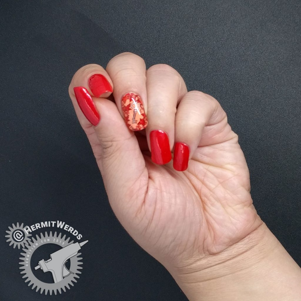 Bright red nail art with a leafy stamping image surrounding a copper key.