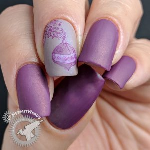 Matte monochrome purple nail art with an ornament hanging from a Christmas tree stamping decal.