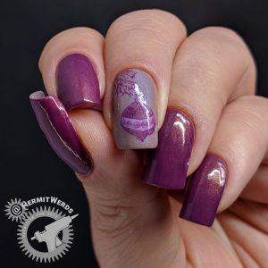Purple nail art with an ornament hanging from a Christmas tree stamping decal.