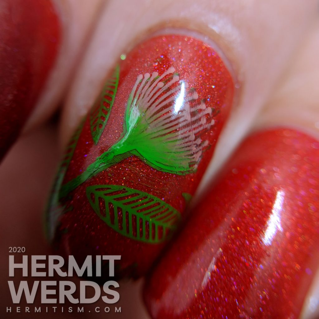 Tomato red nail art with bright green and pink stamped floral and leaf patterns.