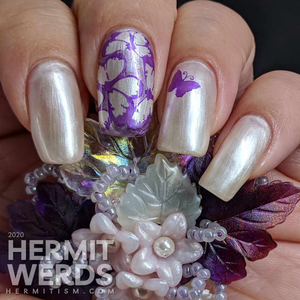 Pearly white/pink sun-activated nail art with purple butterfly stamping.