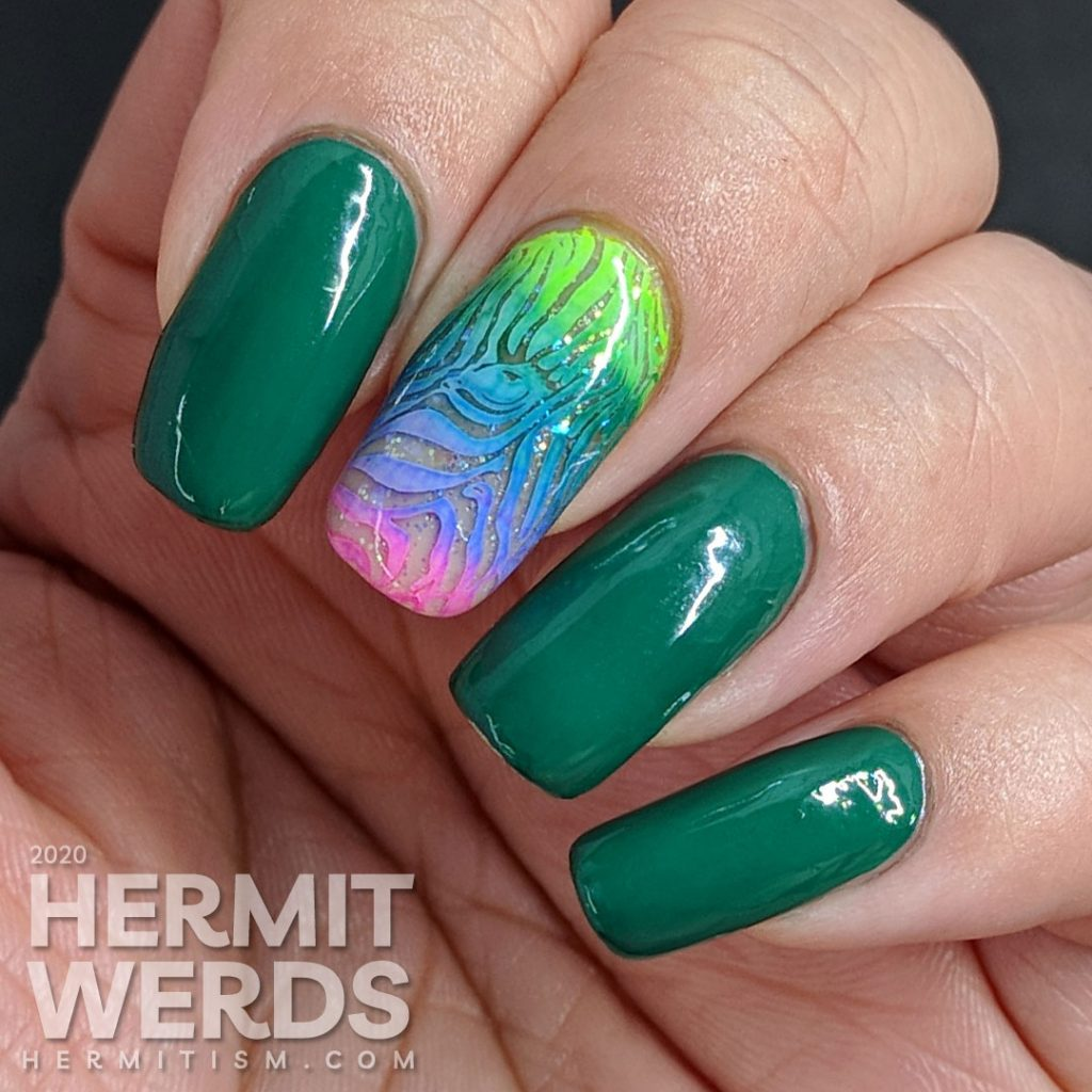 Green nail art with a rainbow zebra accent nail.