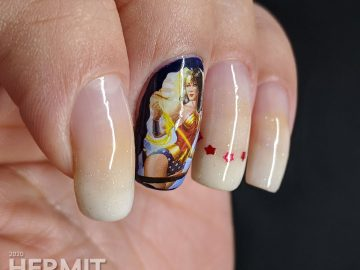Baby boomer french tip nails with a Wonder Woman water decal.
