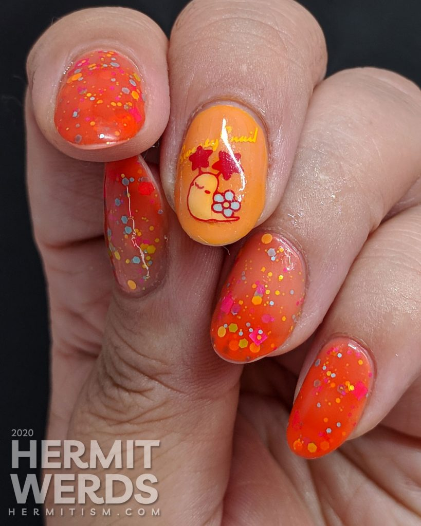 Cute little flower-shelled snail paired with a bright orange to nude crelly polish packed with colorful glitter.