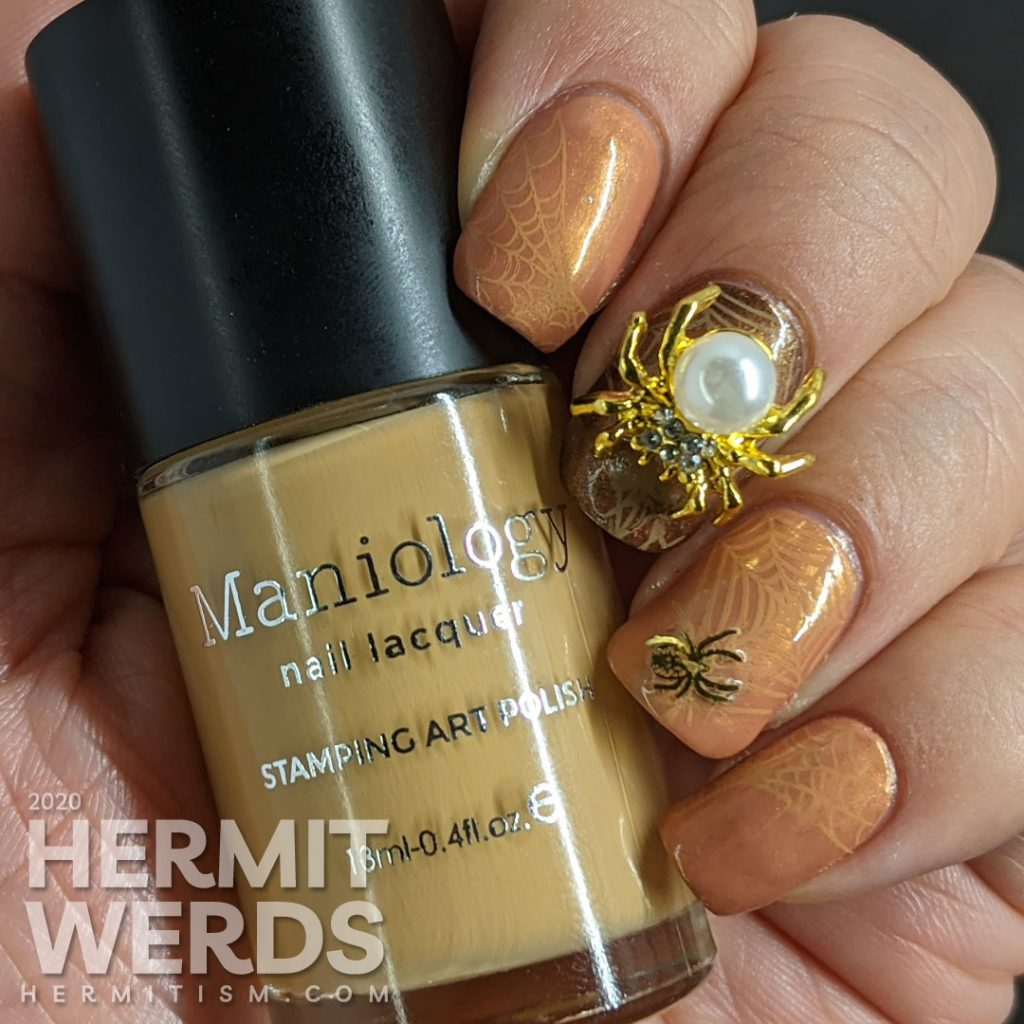 Elegant golden brown nail art with spider web stamping, small metal spider sequins, and a large pearl spider nail charm.