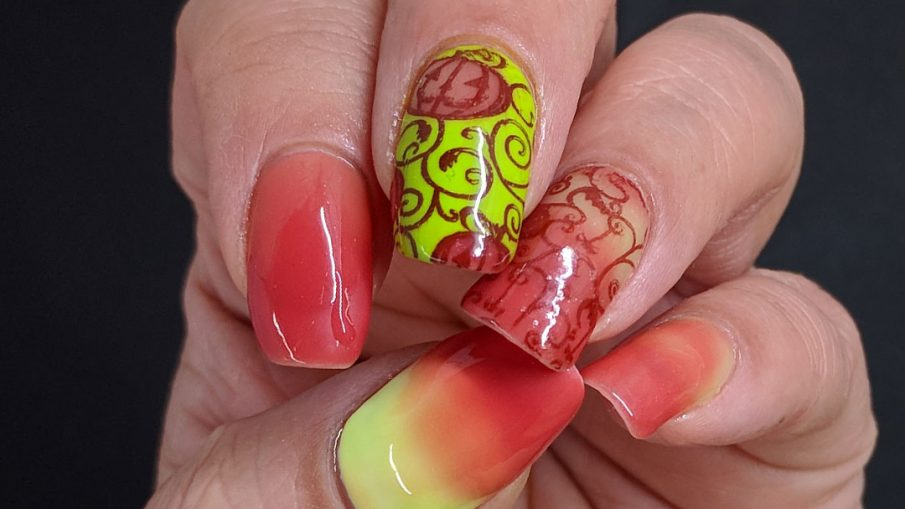 Bright green and coral thermal polish manicure with cute jack-o-lantern pumpkins stamped on top.