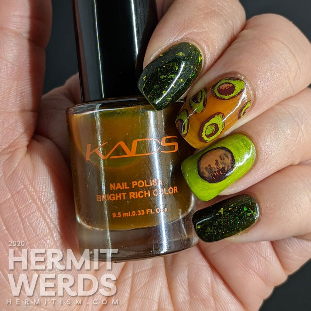 A rich green mani with two accent nails. The first has a brown jelly base and many small avocado decals and the second is a closeup of an avocado with the pit showing.