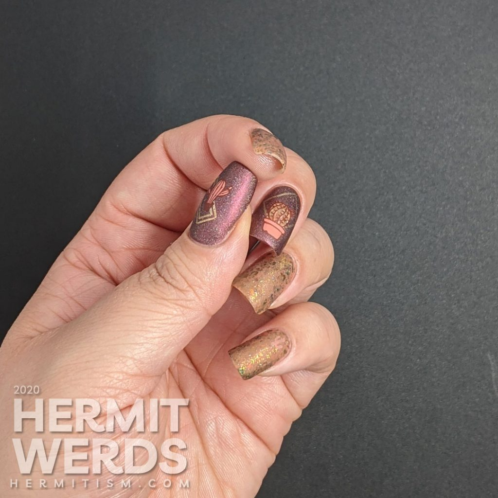 Cactus-themed nail art with a tawny brown and holographic dark red polish and gold geometric frames with potted cacti.