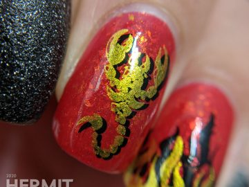 A glow in the dark fire-y thermal red and black nail art with double stamped scorpion and flames and edgy black textured polish accent nails.