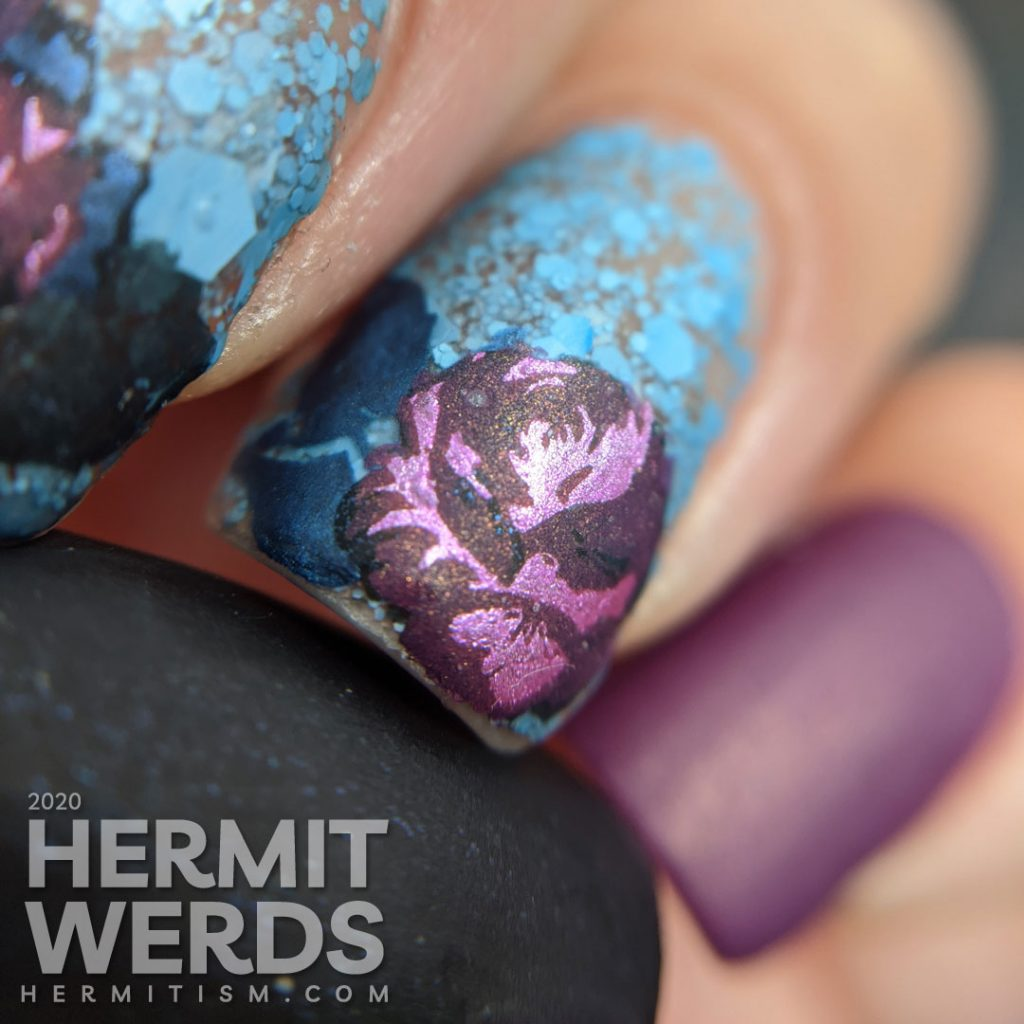 Purple and blue rose-themed nail art with layered stamping roses on a matte blue glitter background.