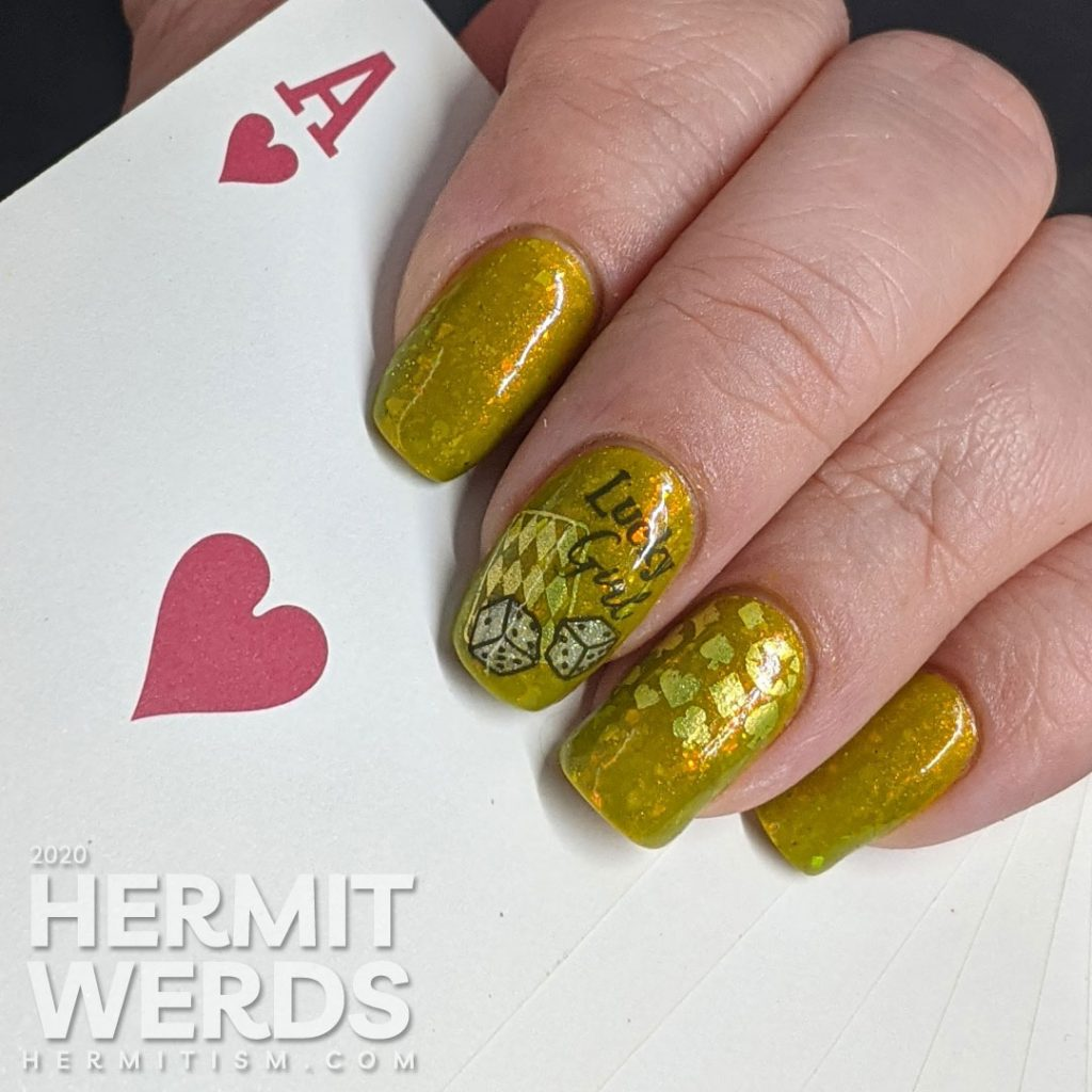 A medium olive/chartreuse nail art with luck, playing cards, dice, and heart/club/spade/diamond stamping decals.