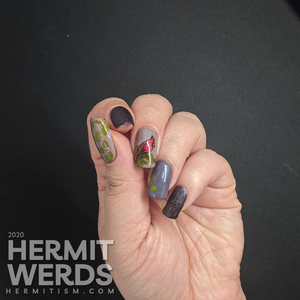A winter nail art with dusty purple polish and bright red cardinal and holly stamping decals on top.