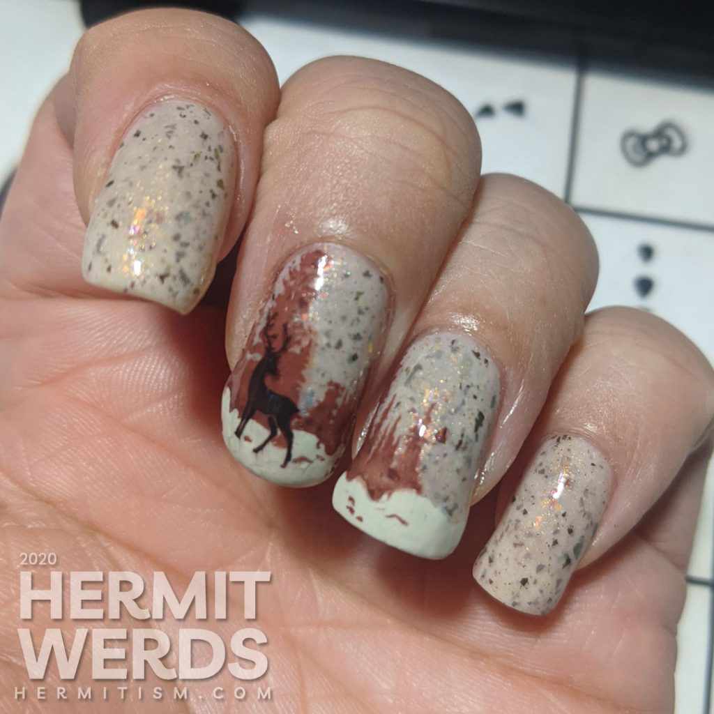 Nail art of a wintery scene with pine trees, mountains, and magical deer on a light tan flakie-filled polish base.