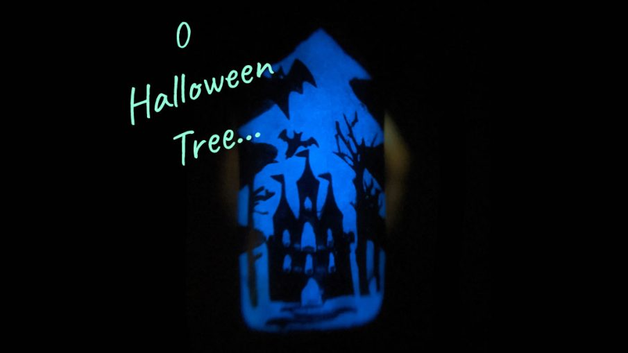 A rainbow glow in the dark mani of silhouetted Halloween images of bats, jack-o-lanterns, haunted castle, spiders, and eyeball candy glowing out from a Christmas tree frame.