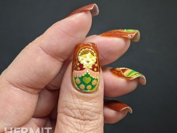 Nail art with stamping decals of beautiful Russian nesting dolls or matryoshka dolls in pinks, reds, and greens on a rusty red background with subtle jelly sandwich.