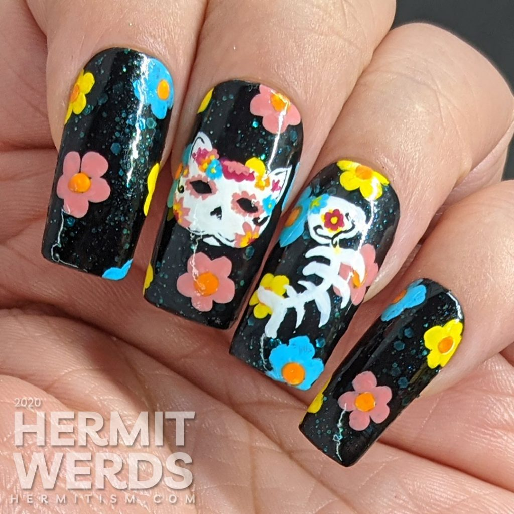 Sugar skull nail art for the Day of the Dead on black jelly teal glitter fake nails with freehand painted cat and fish sugar skulls and flowers.