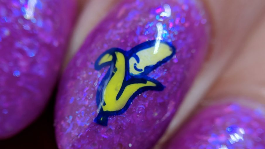 A magenta-purple mani with tons of blue and magenta flakies with a wee little smiling banana stamping decal.