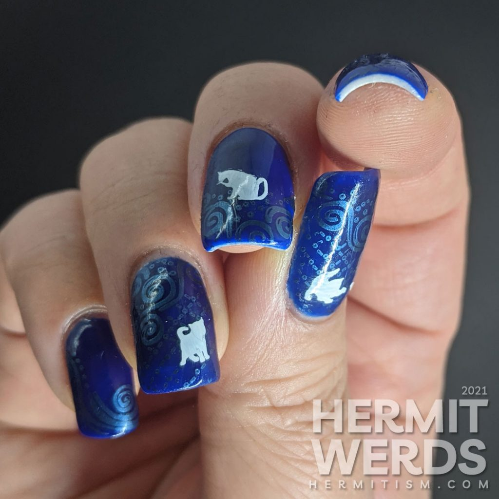 A dark blue nail art with metallic blue decorative swirls stamped in the background and little white cat silhouette stamping decals.