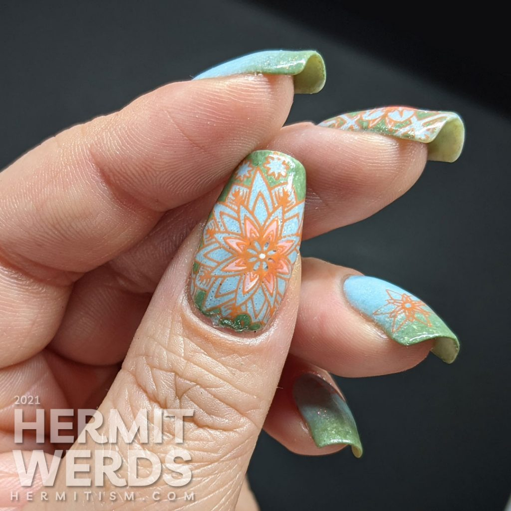 A pastel wintery nail art with snowflake-like flower stamping decals in green, aqua, and orange.