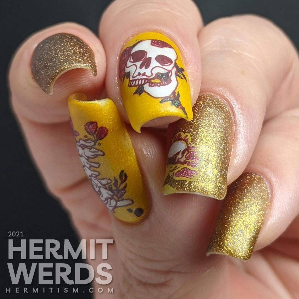 A scattered holographic mustard nail art design with tattoo-like skulls, florals, and rib cage stamping decals.