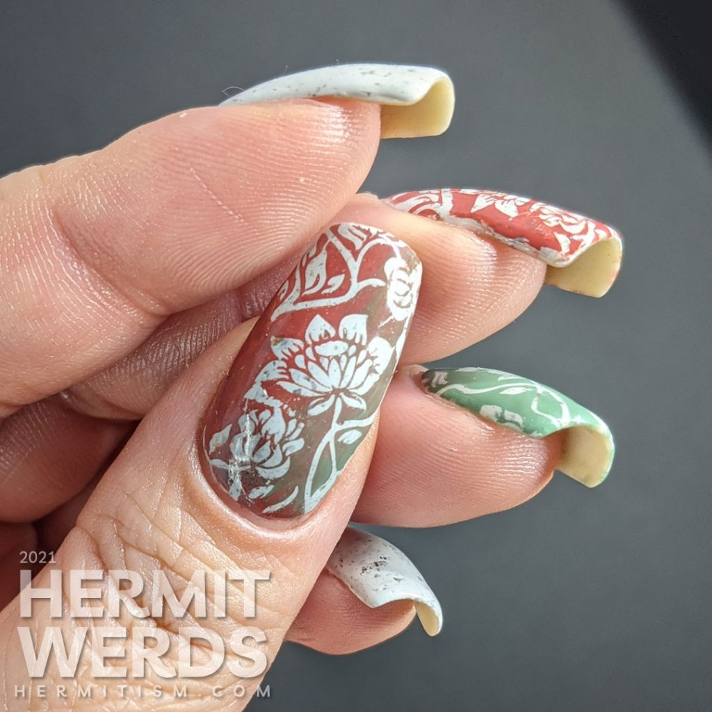 A grey crelly with flakies that shift from red, orange, gold, yellow and green with floral negative space stamps in red and green.