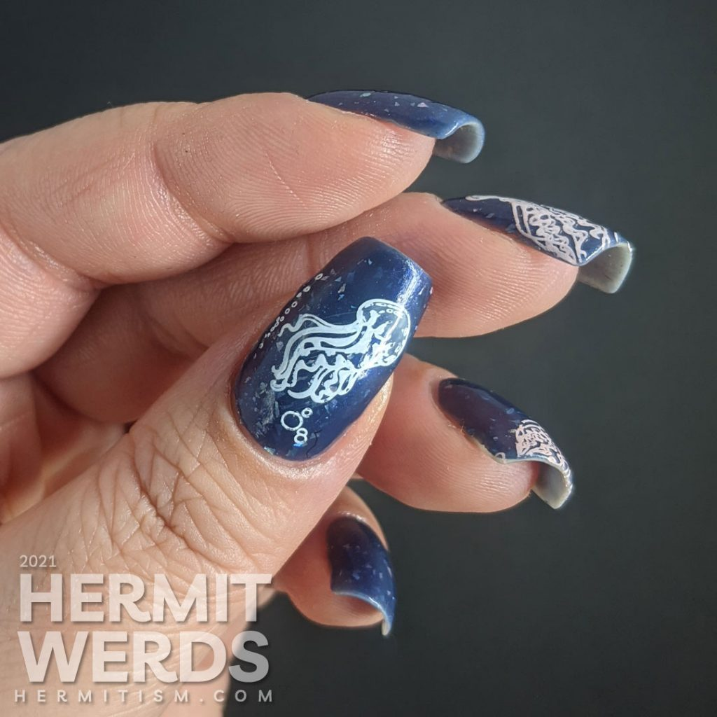 A dusty dark blue mani with transparent jellyfish stamping decals swimming in the sea with little bubbles and flashes of holo.