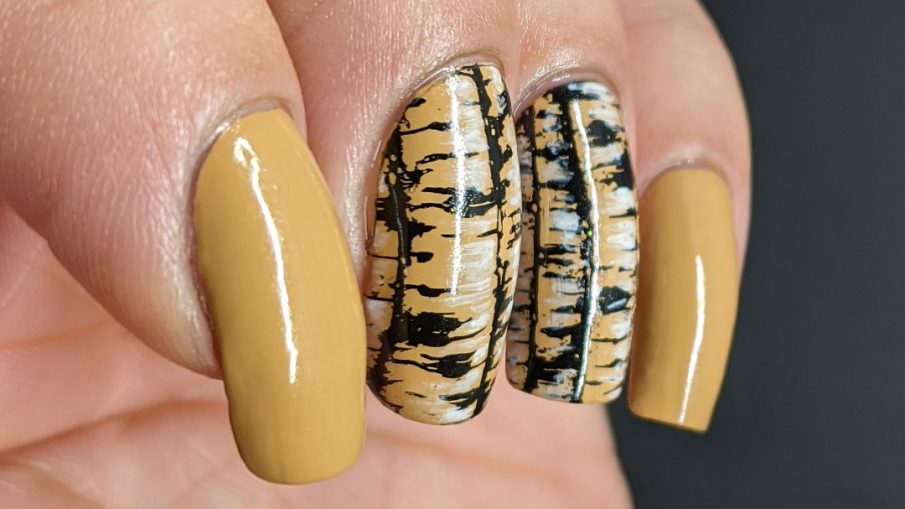 A tan nail art with birch tree trunk stamping images highlighted with white nail polish and frolicking birds.