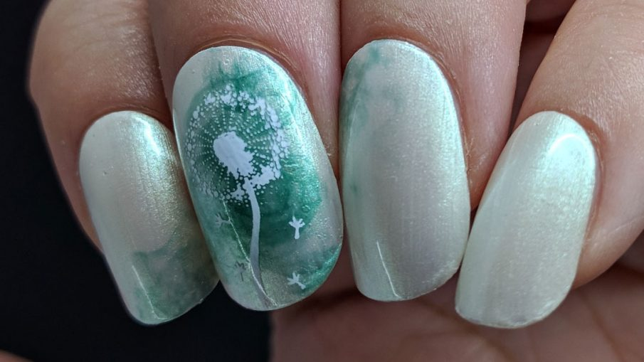 A pearly grey nail art with a soft swirl of green and stamping image of a dandelion puff on top. Done on false nails.