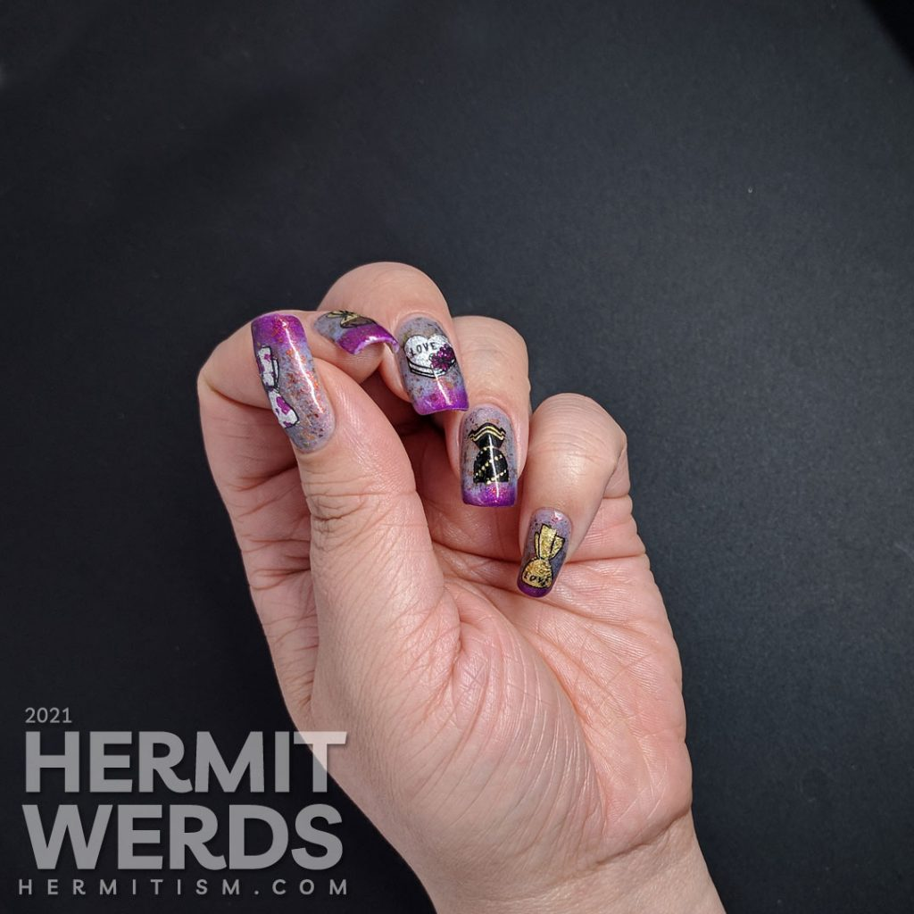 A Valentine's Day candy nail art with nail foil-filled candy stamping decals all on a dusty blue to magenta thermal polish with red to copper flakies.