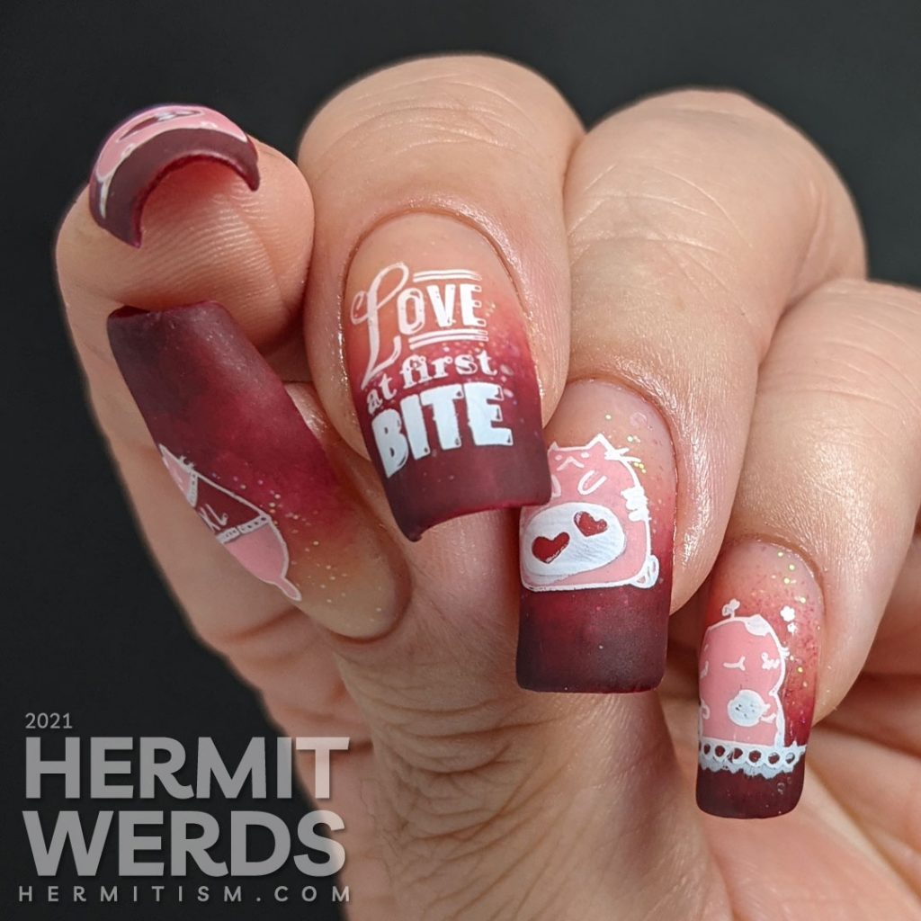 "A dark burgundy to nude with glitter baby boomer French tip with silly hungry cat stamping decals on top and ""Love at first bite"" nail art."