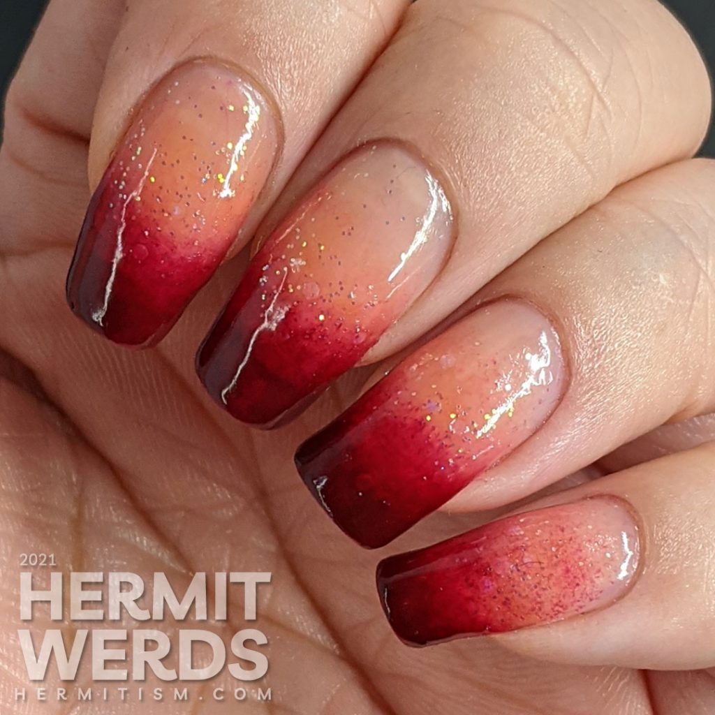 A dark burgundy to nude with glitter baby boomer French tip nail art.