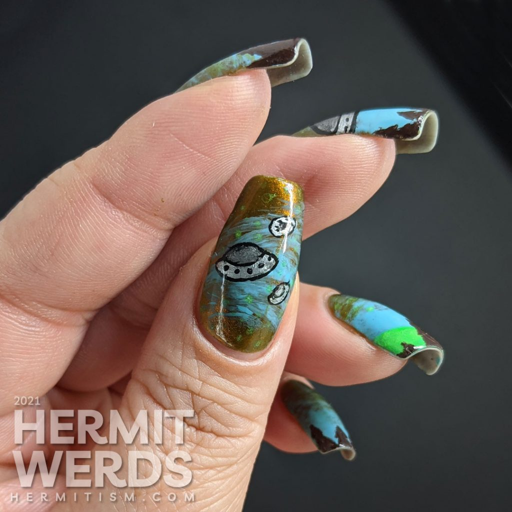 A freehand UFO nail art design with an multichrome olive/red and blue sky, silver UFO with glow in the dark tractor beam and stars.