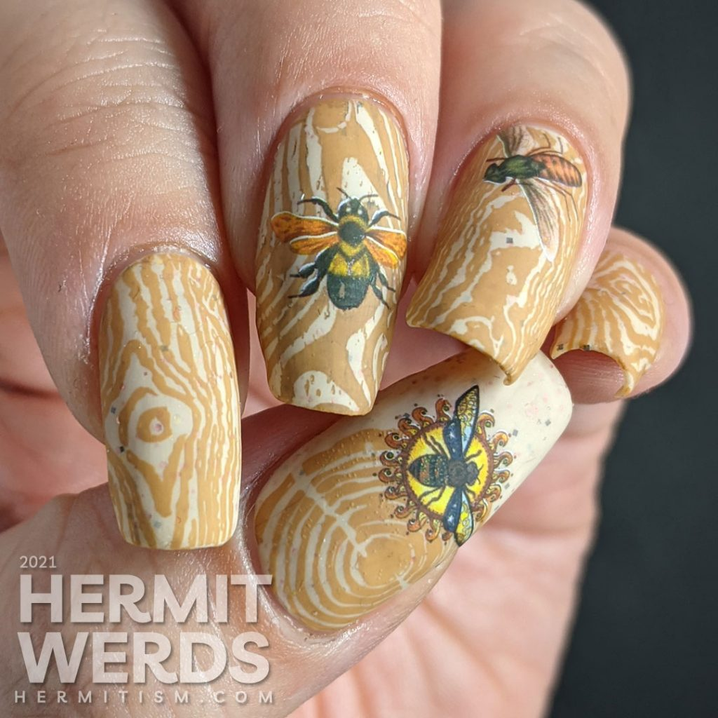 A soft tan and caramel wood texture nail art with bright water decal bugs on top.