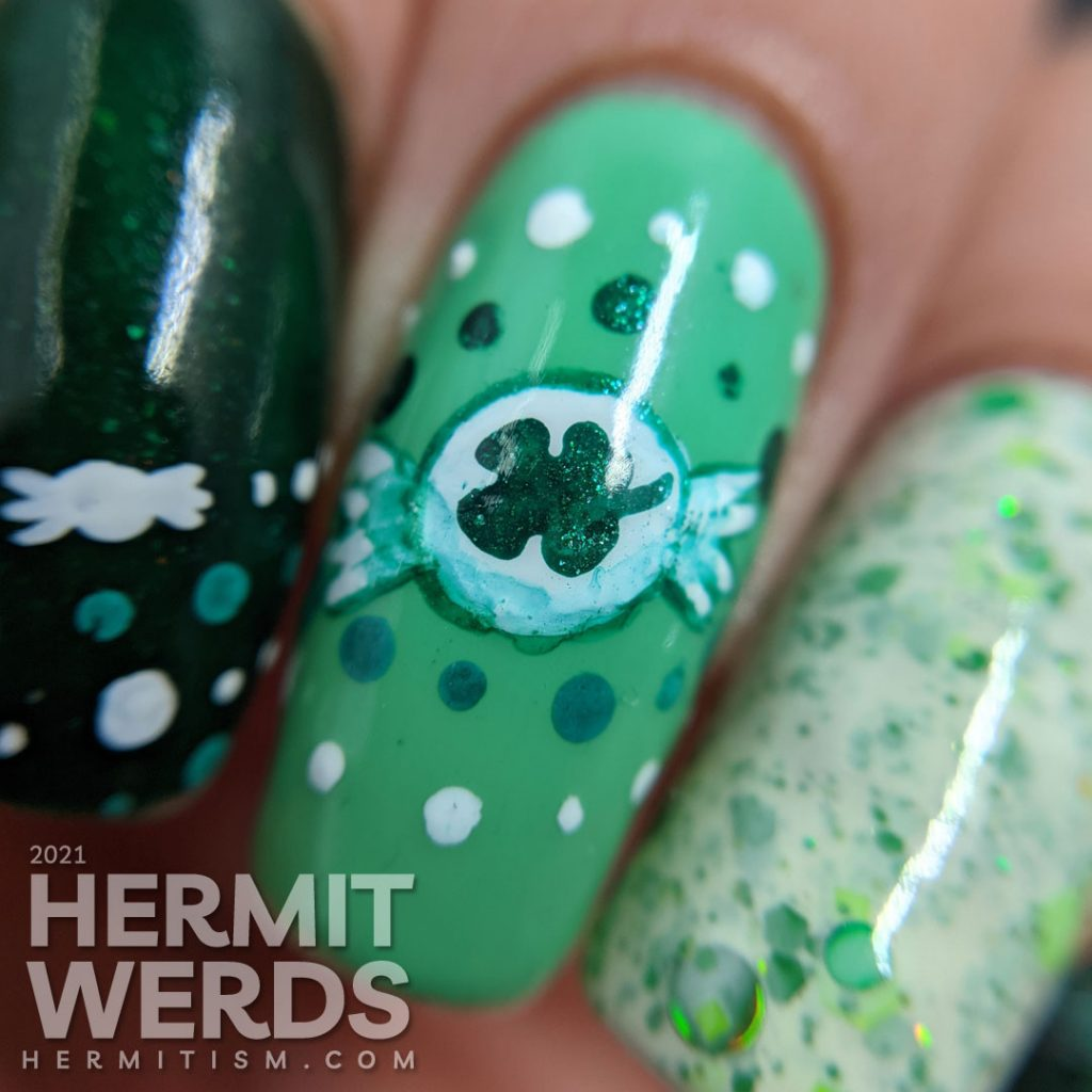 A dotticure clover candy nail art with freehand painted clover hard candies and polka dot patterns.