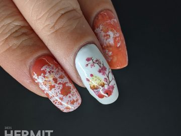 A cupcake nail art with a cupcake water decal accent nail and creamsicle-like water spotted nails in white, orange, and coral.